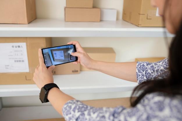 Mujer joven tomando fotografías de cajas de entrega