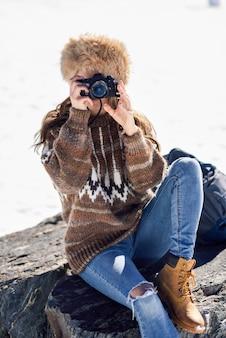 Mujer joven tomando fotografías en las montañas nevadas