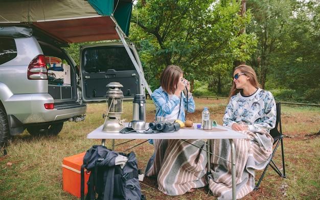 Mujer joven tomando fotos a un amigo feliz mientras desayuna en el camping
