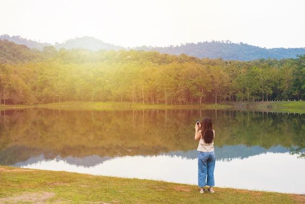 Mujer joven tomando fotos en el camping con reflejo de árbol en agua y cielo hermoso.