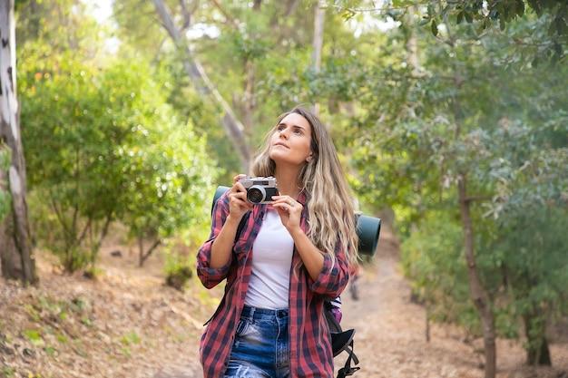 Mujer joven tomando fotos del paisaje con cámara y de pie en el camino forestal. turista mujer caucásica de pelo largo disparar la naturaleza en el bosque. turismo de mochilero, aventura y concepto de vacaciones de verano.