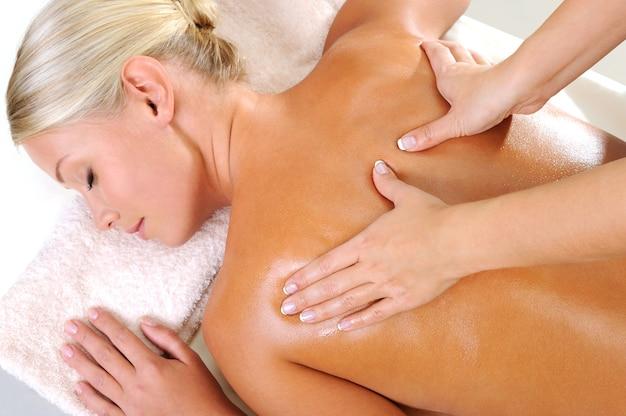 Mujer joven tomando un masaje para su cuerpo en un salón de belleza