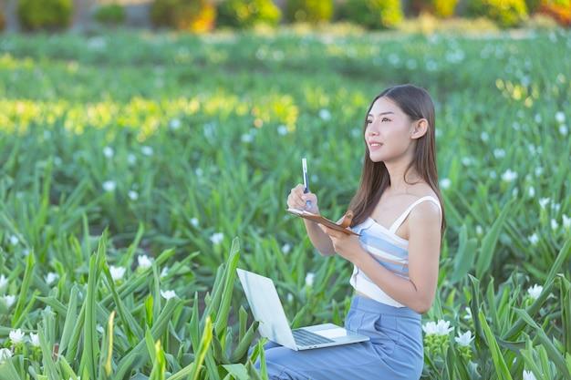 Mujer joven tomando notas en el bloc de notas mientras está sentado en el jardín de flores