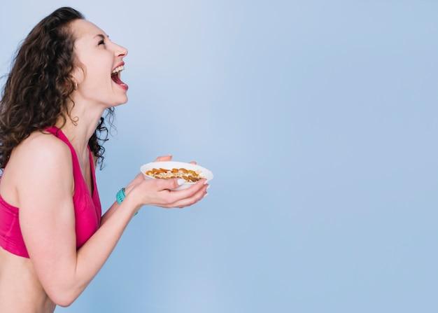 Mujer joven tomando un plato saludable