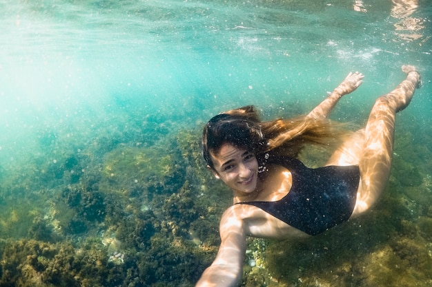 Mujer joven tomando selfie bajo el agua