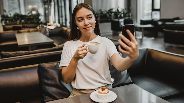 Mujer joven tomando un selfie en la cafetería.