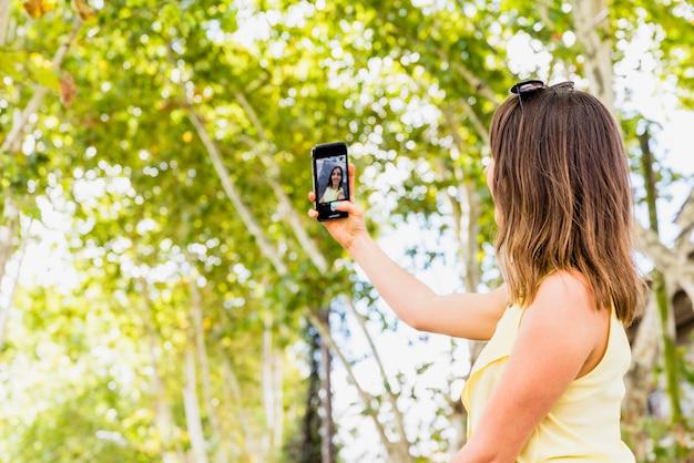 Mujer joven tomando selfie por teléfono en el bosque