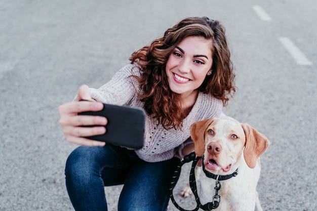 Mujer joven tomando un selfie con teléfono móvil con su perro en la calle