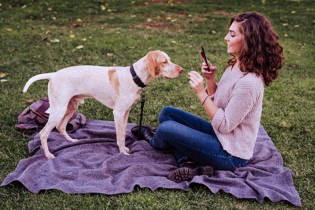Mujer joven tomando un selfie con teléfono móvil con su perro en el parque