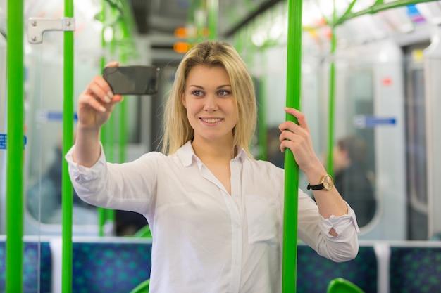 Mujer joven tomando un selfie en el tren de metro de londres