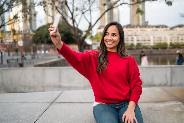 Mujer joven tomando selfies con teléfono.