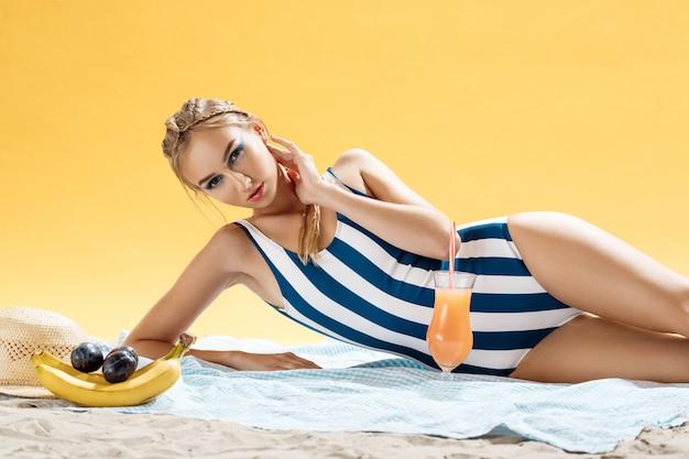 Mujer joven tomando el sol con traje de baño a rayas