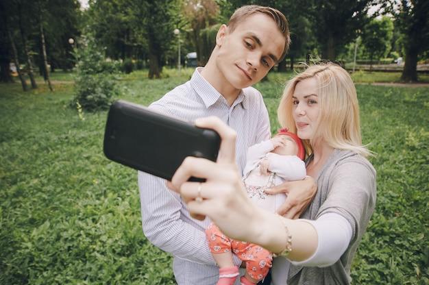Mujer joven tomándose una foto con su pareja y su bebé