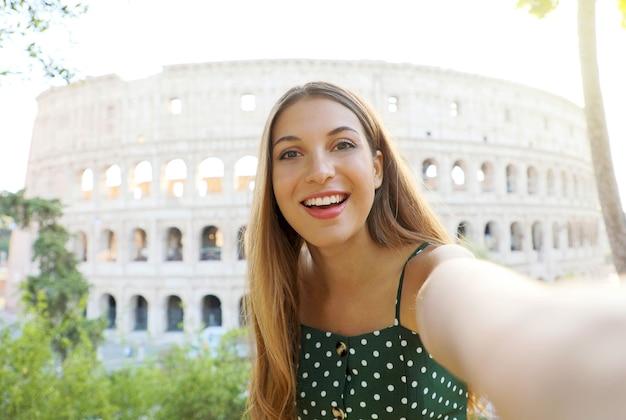 Mujer joven tomar autorretrato con detrás del coliseo en roma, italia