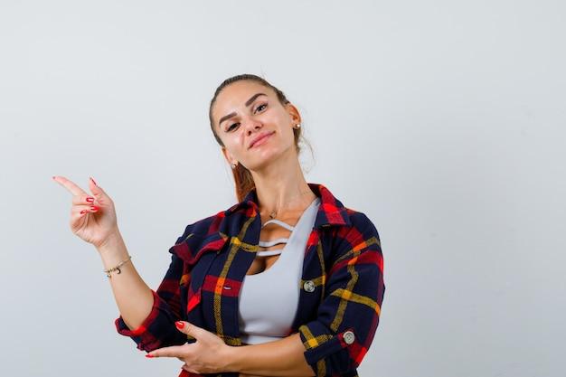 Mujer joven en top corto, camisa a cuadros apuntando a la esquina superior izquierda y mirando confiada, vista frontal.