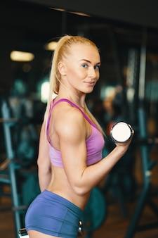 Mujer joven en top rosa y mini shorts haciendo ejercicio con pesas