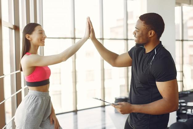 Mujer joven en un top rosa de pie con un entrenador