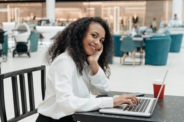 Mujer joven trabaja en una computadora portátil en un café shopping mall