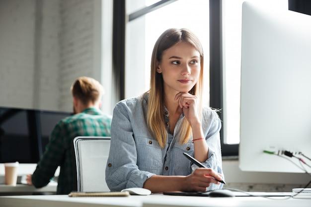 Mujer joven trabaja en la oficina con computadora y tableta gráfica