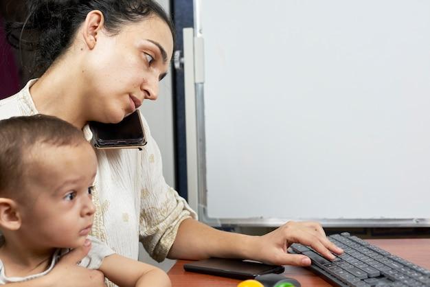 Mujer joven trabajando en casa y sosteniendo a un bebé