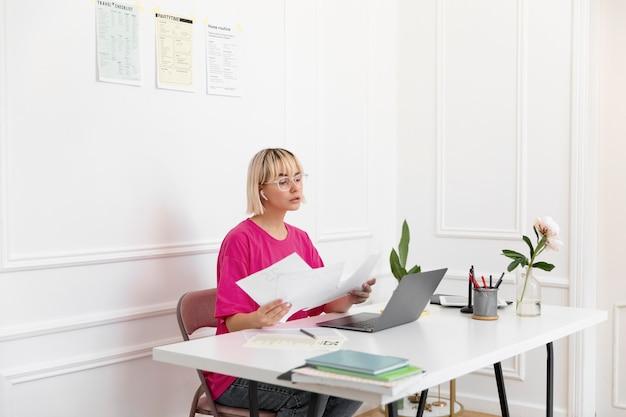 Mujer joven trabajando desde casa en su computadora portátil