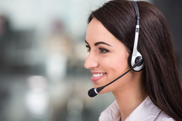 Mujer joven está trabajando en un centro de llamadas.