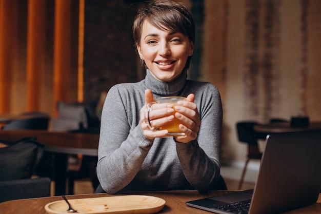 Mujer joven trabajando en la computadora y bebiendo té caliente