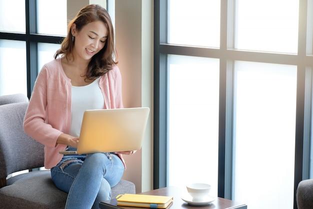 Mujer joven trabajando negocios en línea usando la computadora portátil con sorbos de café en un estado de ánimo cómodo.