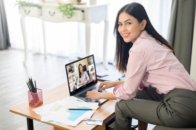 Mujer joven está trabajando con la pantalla de su computadora durante una reunión de negocios a través de la aplicación de videoconferencia.