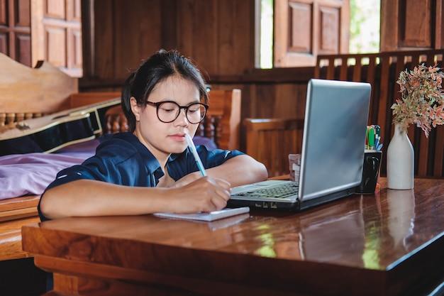 Mujer joven trabajando sentado en el sofá con el portátil en casa