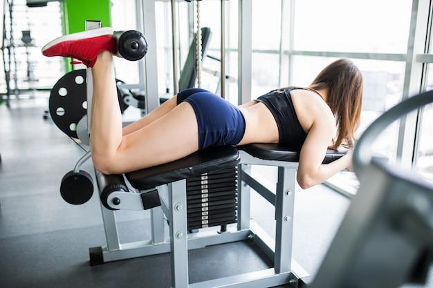 Mujer joven trabajando sus quads en la máquina de prensa en el gimnasio.