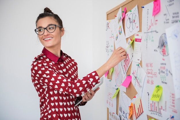 Mujer joven trabajando en tablón de anuncios en la oficina
