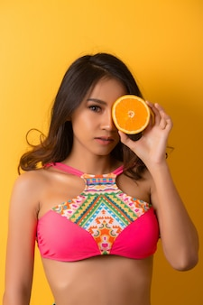 Mujer joven en traje de baño aislada sobre amarillo