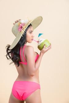 Mujer joven en traje de baño con coco