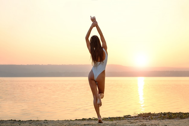 Mujer joven en traje de baño de cuerdas se encuentra en la playa al amanecer.