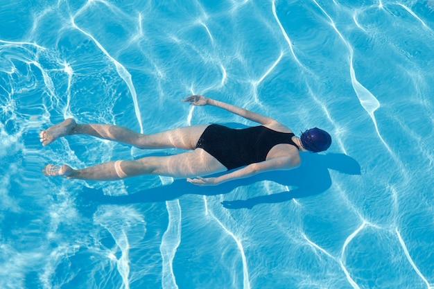 Mujer joven en traje de baño deportivo gorra nadando bajo el agua