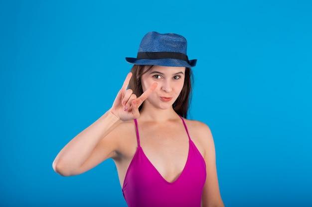 Mujer joven en traje de baño lila lencería y sombrero con gestos con las manos aisladas en azul