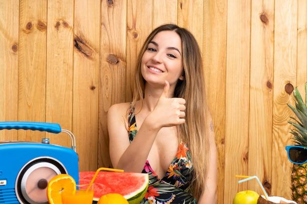 Mujer joven en traje de baño con un montón de frutas dando un pulgar hacia arriba gesto