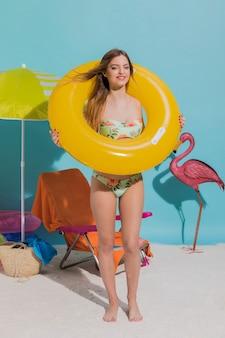 Mujer joven en traje de baño posando con salvavidas amarillo