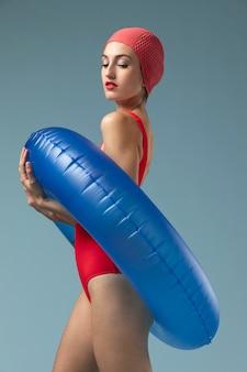 Mujer joven con traje de baño rojo y un anillo de natación