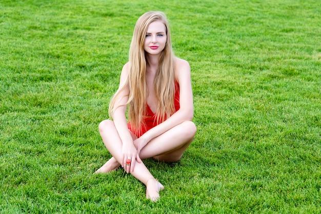 Mujer joven en traje de baño rojo tomando el sol en la hierba. ocio de verano, al aire libre en el parque en el resort de lujo.