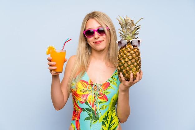 Mujer joven en traje de baño sosteniendo una piña con gafas de sol