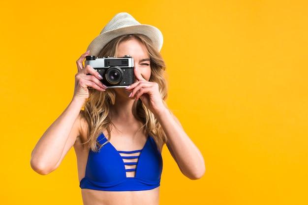 Mujer joven en traje de baño tomando foto