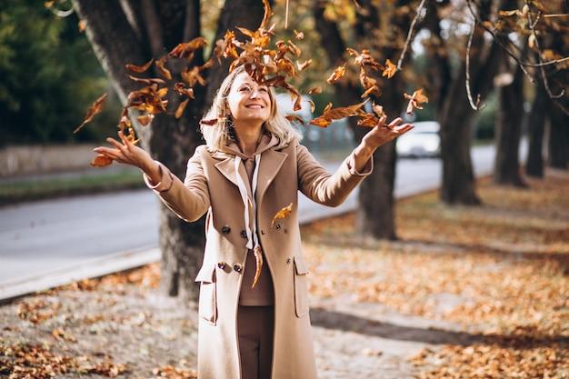 Mujer joven en traje beige afuera en un parque de otoño