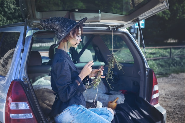 Mujer joven en un traje de bruja sentada en el maletero del coche