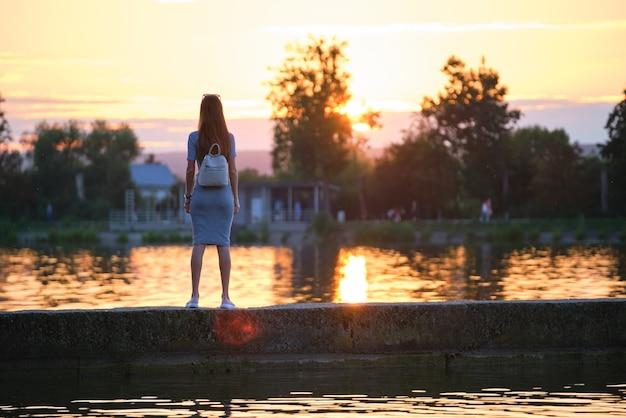 Mujer joven en traje casual relajante en el lago en una cálida noche. vacaciones de verano y concepto de viaje.