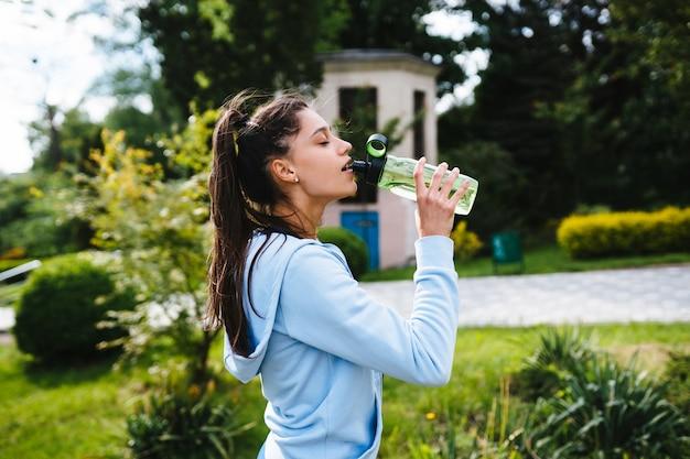 Mujer joven en traje deportivo bebe agua de una botella después de la gimnasia al aire libre en el verano