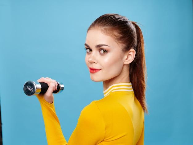Mujer joven en un traje deportivo de color amarillo brillante con pesas hace deporte en un azul