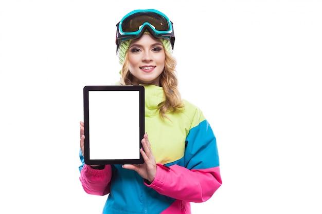Mujer joven en traje de esquí mostrar tableta vacía