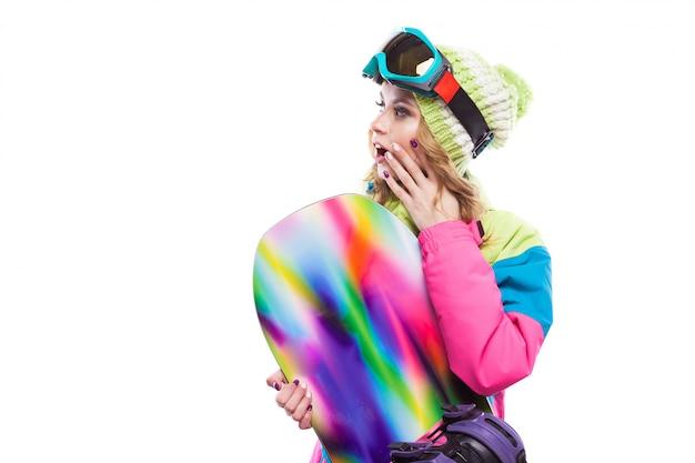 Mujer joven en traje de esquí con tabla de snowboard